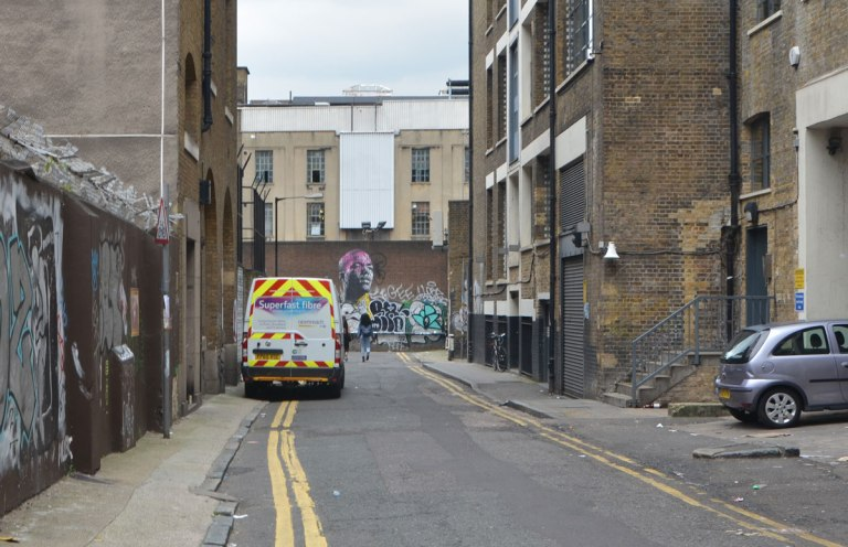 a truck painted in yellow and red stripes is parked on the side of a narrow street, brick three storey buildings on either side, graffiti on the wall at the end of the lane