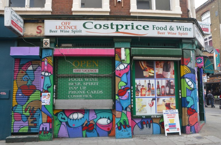 a photo of a costprice store, an off licence beer, wine and spirits merchant, as well as food. A painting of multicoloured colourfuil abstract faces covers all surfaces.
