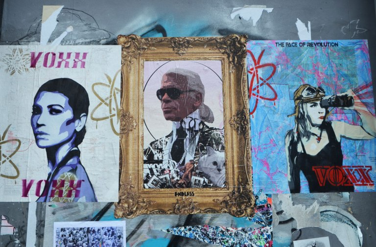 three pasteups on a wall, poster size, two by voxx and one in the middle by endless. Karl Lagerfeld is the subject in the endless paste up - with dark sunglasses and a wild patterned jacket, a fancy gold frame is around him,