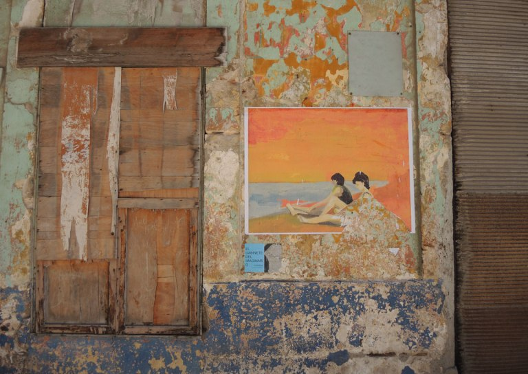 a rough wooden cover covers a window, a wall used to be orange and blue but most of the paint has peeled off. On the wall a picture has been mounted. It is a beach scene, two people sitting on an orange beach with orange sky and blue water.