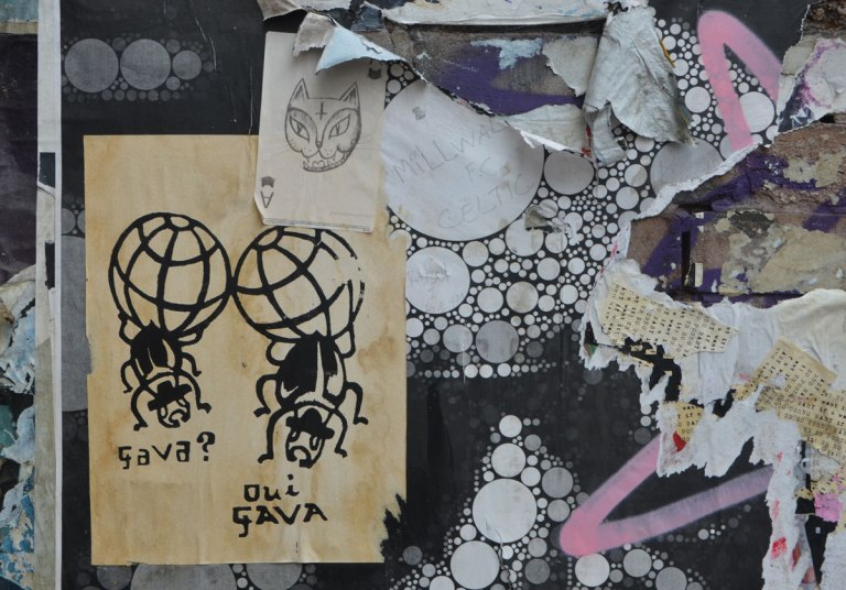 graffiti and street art on fashion street in shoreditch east london, paper paste up of a drawing of two insects with large globe like tails, one is asking gava? and the other says oui gava