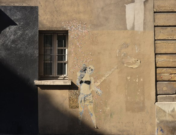 large size paper paste up of a young woman, standing, with a lot of small glittery pieces of paper scattered around her - wearing a black bra top and shorts