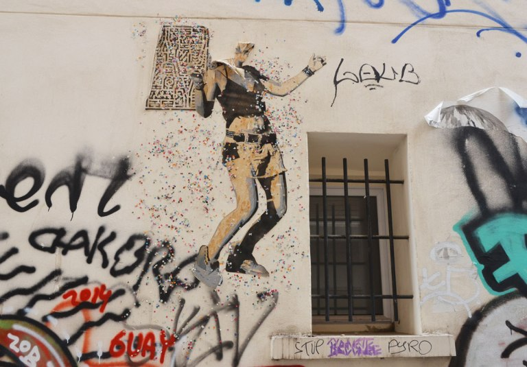 large size paper paste up of a young woman, standing, with a lot of small glittery pieces of paper scattered around her - wearing shorts with a belt, a wide bracelet. The top of her head has been ripped off. She seems to be dancing beside a window