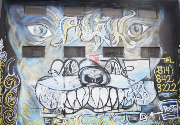 street art, graffiti, animals painted on a wall - a large dog face on a garage door that has been partially tagged over