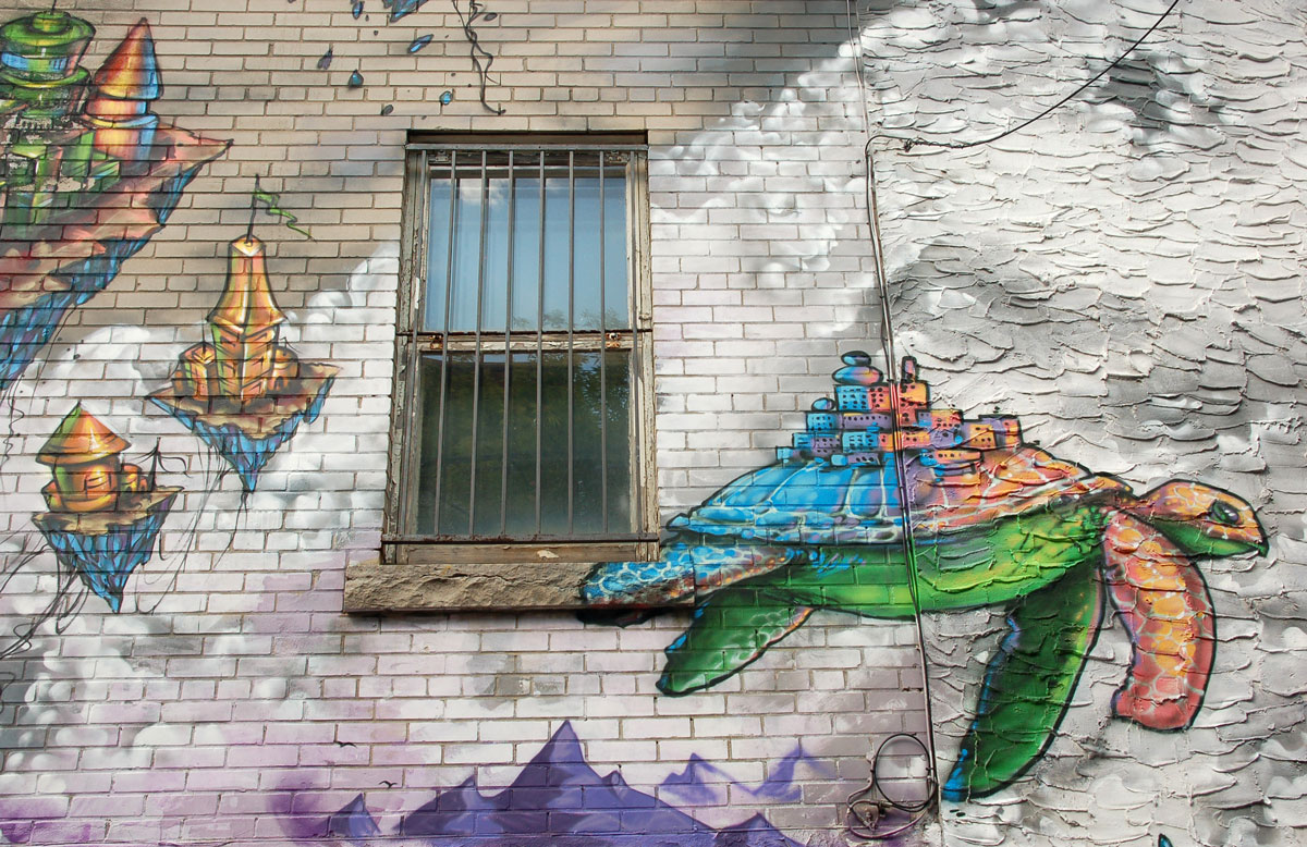 street art, graffiti, animals painted on a wall - a turtle flying in the clouds past a real window, with small buildings on its back