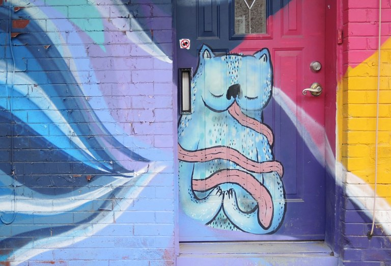 street art, graffiti, animals painted on a wall - blue cat with a very long pink tongue that encircles its body a couple of times, sitting in a doorway