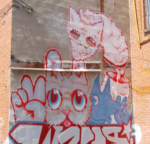 street art, graffiti, animals painted on a wall - a pink cat and blue dog, both giving a peace sign