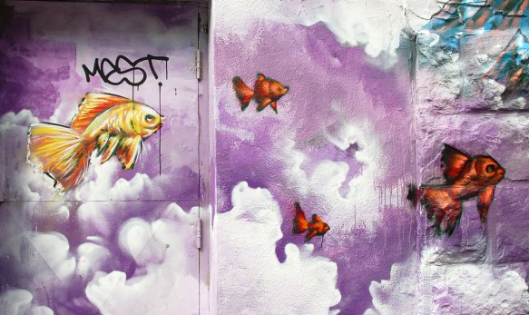 street art, graffiti, animals painted on a wall - yellow and orange fish swimming in a purple sky with puffy clouds