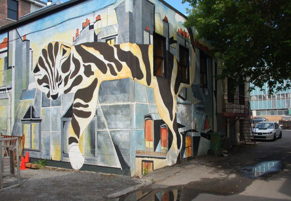 mural of a large tabby cat lying on rooftops with its paw hanging over the side of the buildings