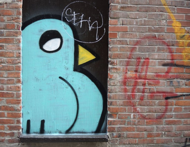 street art, graffiti, animals painted on a wall - a large stylized pale blue bird in a window of a red brick building.