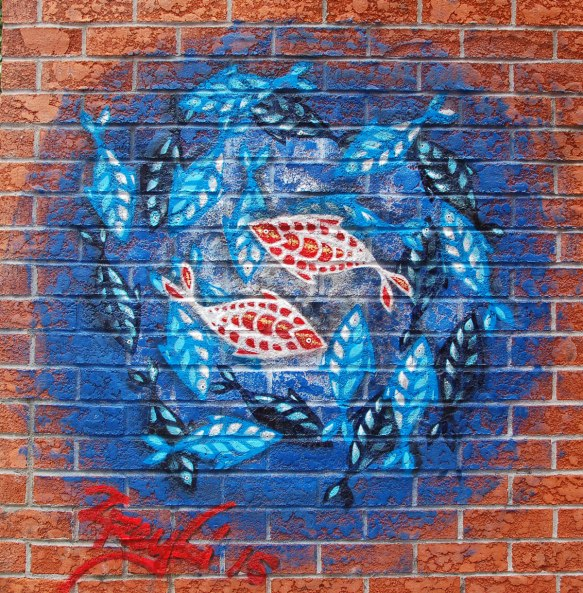 street art, graffiti, animals painted on a wall - a blue circle with concentric patterns of fish in reds, blues and blacks