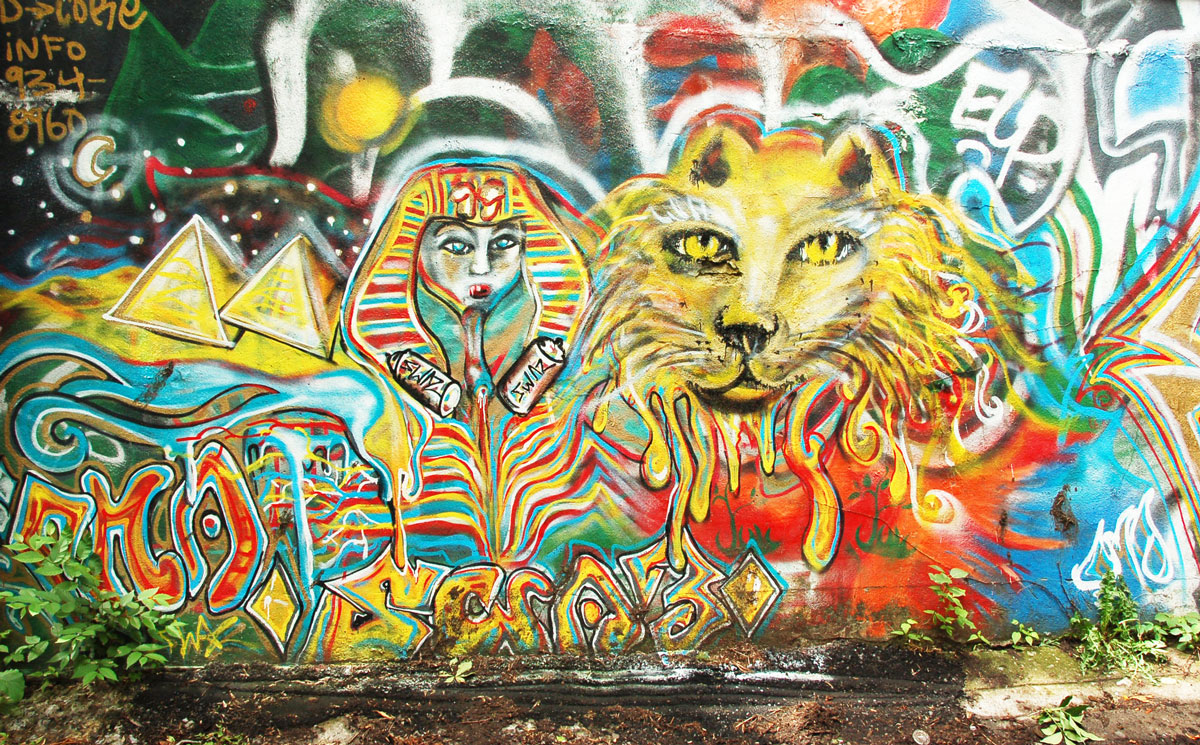 street art, graffiti, animals painted on a wall - a lion head in an Egyptian themed mural, a pharaoh head, and pyramids are also in the picture