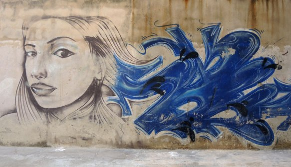 a street art picture of a young woman's head and face, she is looking slightly back over her shoulder. Blue abstract beside her