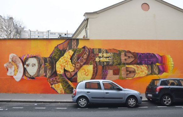 man in a long horizontal mural, cloth puppet like face, dressed in a patchwork of colours and patterns and Inca and South American symbols, two gold good luck charms attached to his belt.