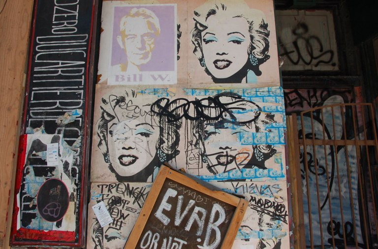 5 poster of Marilyn Monroe on a wall. The 6th poster has been covered by a poster of a man, Bill W.