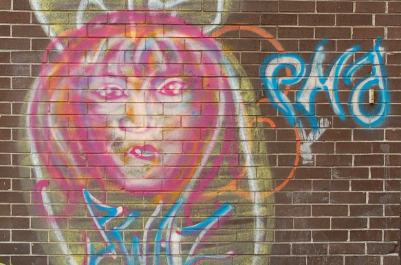 painted face on a brick wall, pink and yellow