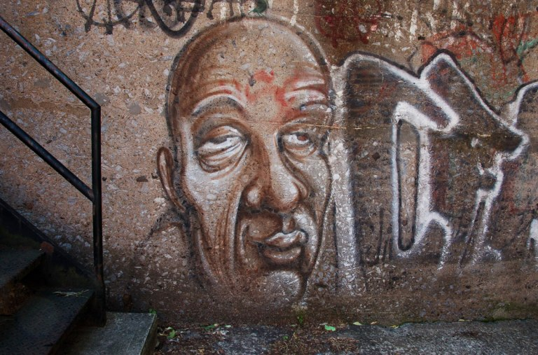 brown street art painting of a blad man's head and face with droopy eyes partially closed and wrinkled foreheard and cheeks