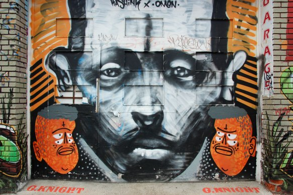 large black and white man's face painted by omen with a small orange face to the bottom left and bottom right - orange faces painted by kashink