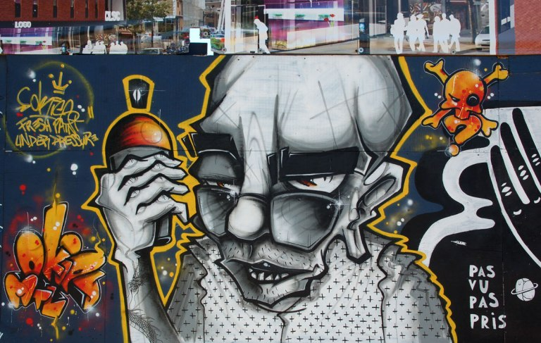 fresh paint under pressure, a man is holding a spray paint can. he is old looking, bald, with glasses at the end of his nose, wearing a top with black polka dots, done in grey tones