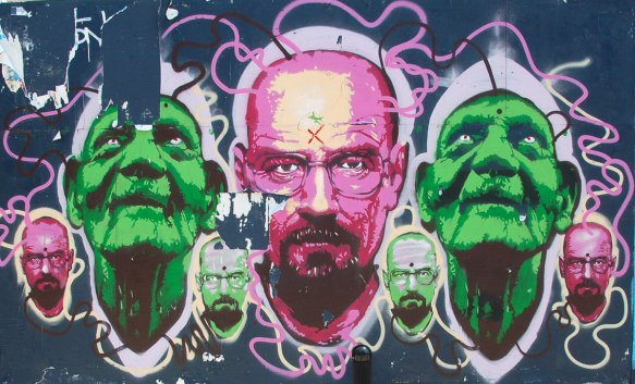 three mens heads. in the center, a bald man in pinks. on either side of him, the identical green man looking upwards.