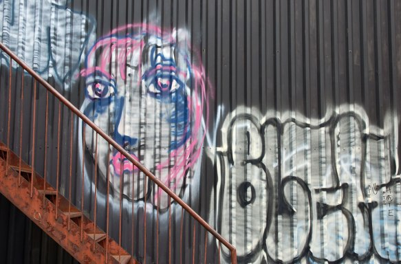 a face painted on a brown metal wall beside an exterior stair case