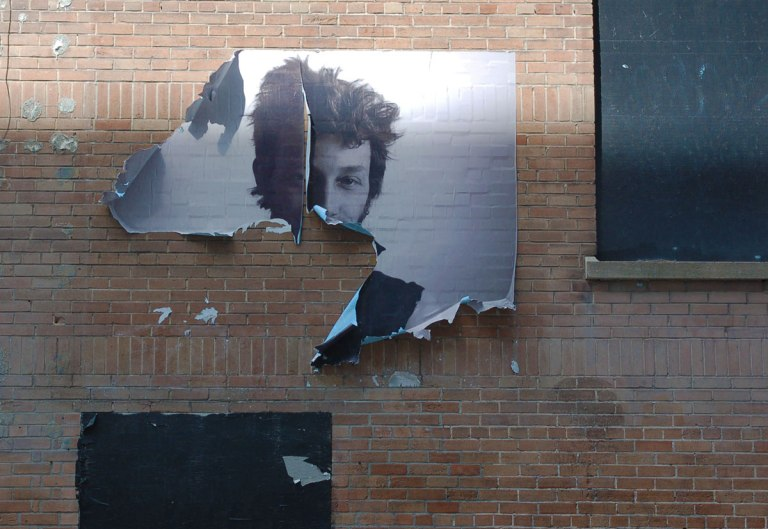 a paste up of a black and white photo of a young man that is torn and the bottom half is missing