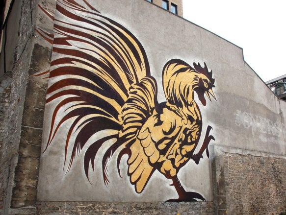 mural painting of a very large yellow and brown rooster on the side of two storey building in downtown Montreal