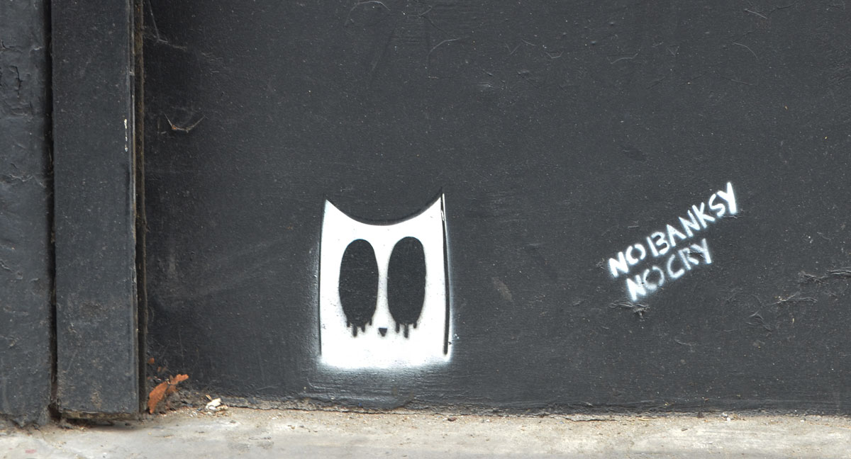on a black wall, two small stencils, one is a white ghost head with big black oval eyes and the other is the words: no banksy no cry