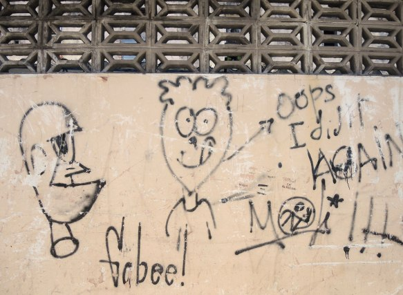 scribbled graffiti on a wall, a silly drawing of a boy with the words oops I did it again, some exclamation marks