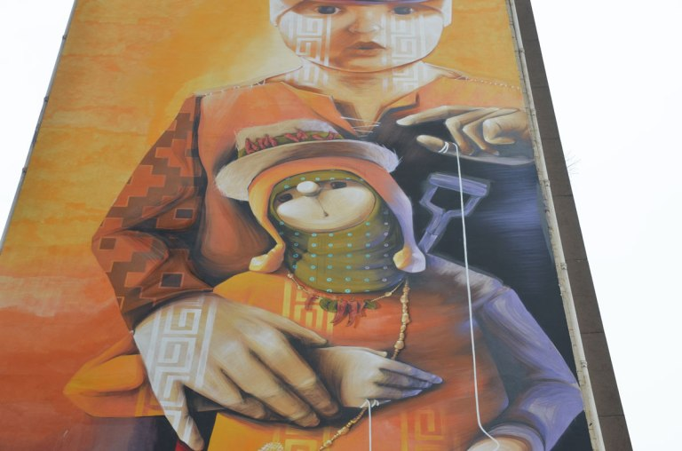 part of a large multi storey vertical mural on the side of an apartment building in Paris called 'Our Utopia is Their Future' by inti - a child is working a puppet who in turn has a small puppet on a string