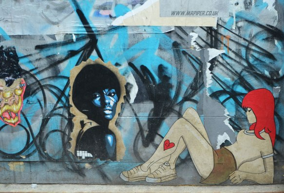 3 paste ups of women on a wall. One is a woman's head and shoulders in blue with short black hair by iljin . One is a multicoloured face. One is a young woman sitting on the ground with her knees up. She has red hair and a heart on her leg, by c3b