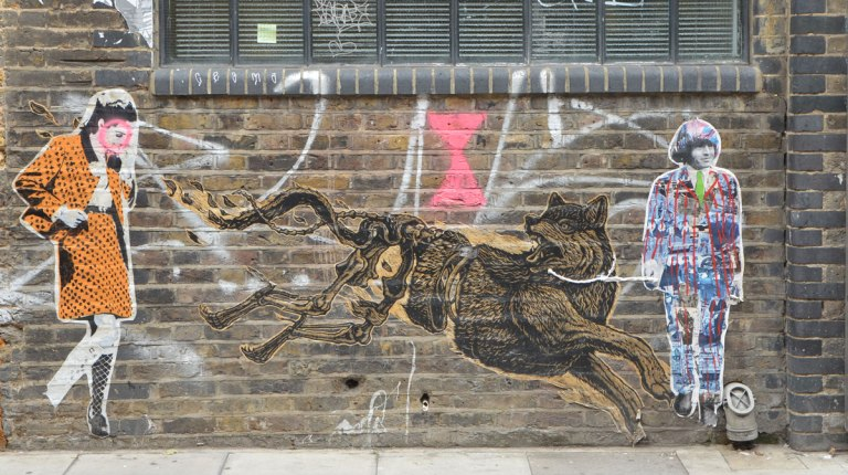 three large pasteups on a brick wall, a woman in an orange skirt and jacket by endless, a large growling dog who is running - head and front part of body are complete, back part of body is just the skeleton, and last is a man with longish hair, a multicoloured suit and a green tie.