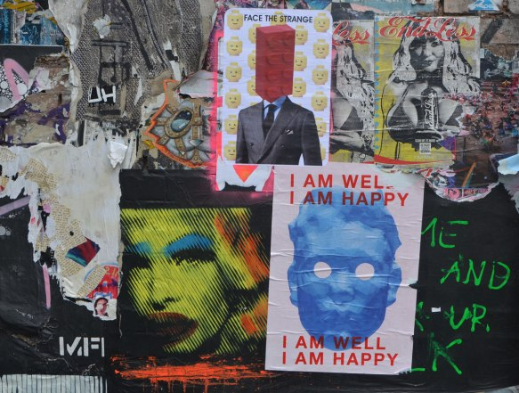 pasteup on a wall, collage of overlapping layers of pictures, jumbled up together,