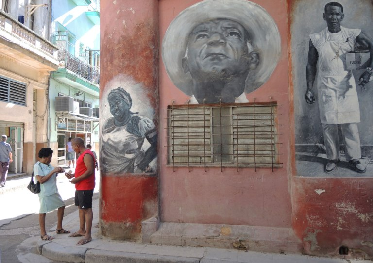 a man and a woman talking on a street corner. Beside them is a wall with three black and white murals painted on it. A middle ages woman with a head band and hands on her hips, an older man's head in a white hat and looking upward and last, a man in a white uniform holding a box under his arm.