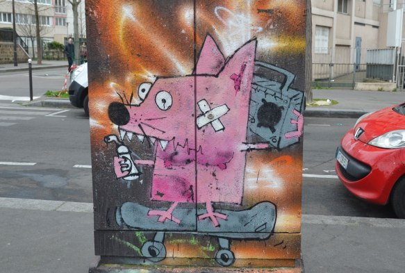 on a metal box on the sidewalk pavement beside a street, a pink squarish creature with a band aid on its cheek rides on a skateboard while holding a ghetto blaster near its ear, a spray paint can in its other hand