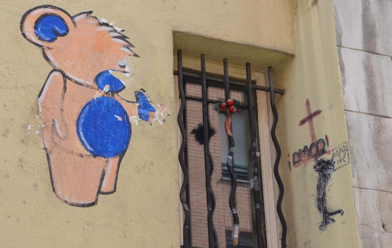 a pink and blue teddy bear paste up pon a wall, partially torn. He's beside a window. on the other side of the window is a small red cross with the word amor written under it.