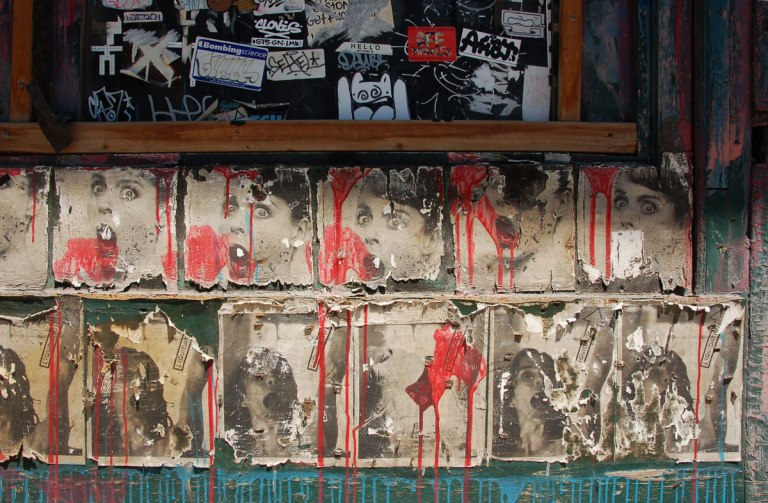 two rows of repeating posters. In browns, faded, with torn edges, and red paint blobs and drips on top of them. The top row is girl's head and the bottom is a young girl looking up