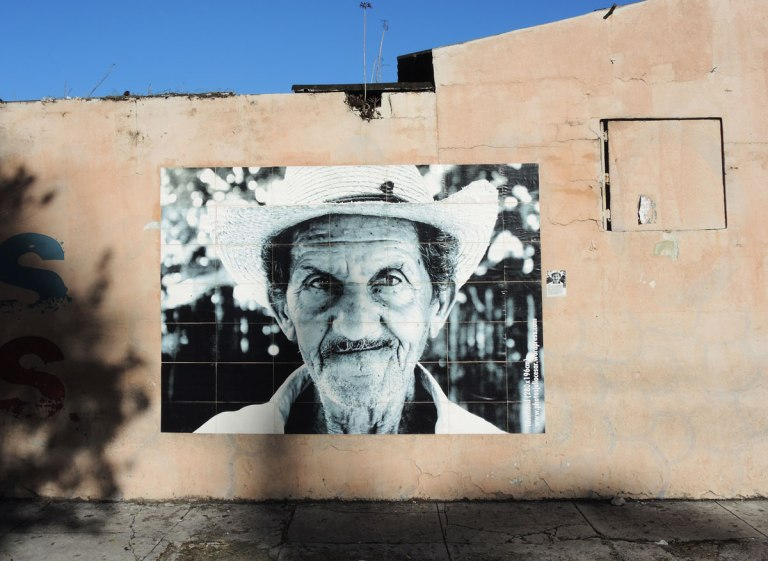 a black and white photo of a man's head and shoulders, wearing a white hat, older man, large picture, on a wall outside