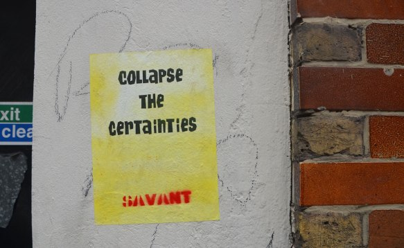 stencil on a wall. poster sized, words by savant that say Collapse the Certainties.