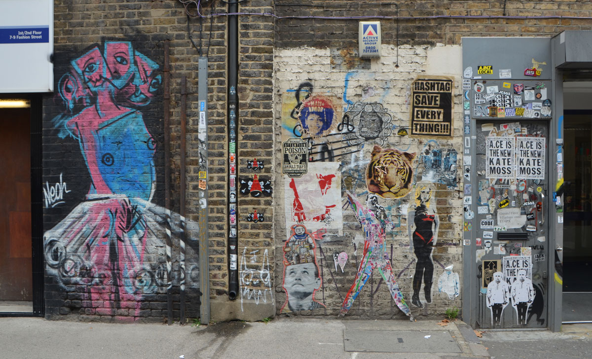 wall with lots of street art and graffiti, paste ups and posters