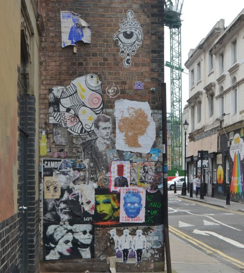 a brick wall on Fashion Street in Shoreditch that is covered with a lot of paste up pieces of graffiti and street art