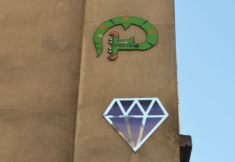 two graffiti pieces on a wall, a blue and silver diamond shape an a green snake