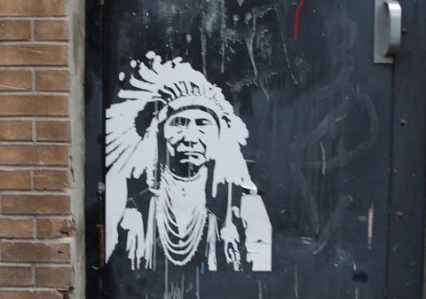 a white stencil of an older Indian (first nations) man in a feather head dress. A stereotypical picture of Indian chief from old pictures