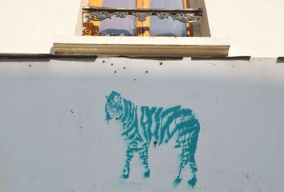stencil graffiti of a greenish coloured striped zebra