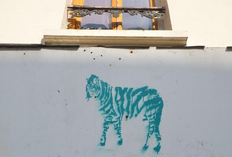 stencil graffiti of a greenish coloured striped zebra