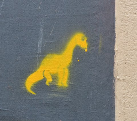 stencil graffiti of a little yellow dinosaur