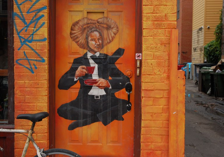 street art painting on a bright orange door of a man in a suit sitting cross legged with a cup and saucer of tea. red tea cup and red saucer. his tie is flipped up and his hair is weird he is Monsieur Croissant Head
