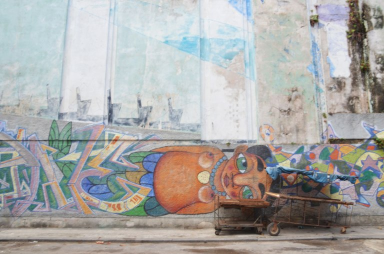 a wooden cart in poor shape is parked next to a mural of a woman lying on her side. It looks like she is lying on the sidewalk. She is topless.