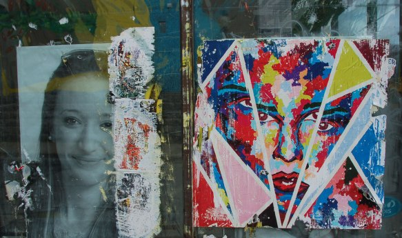 two paste ups on an old window. on the left is a black and white photo of a young woman. on the right is an abstract of a face in bright primary colours, fractured so she has 4 eyes