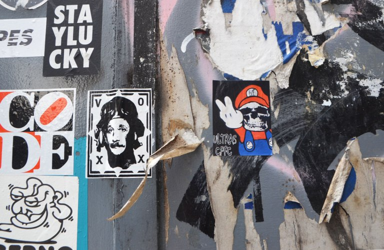 stickers and paste ups graffiti on a wall, Mario brothers parody, man by voxx,